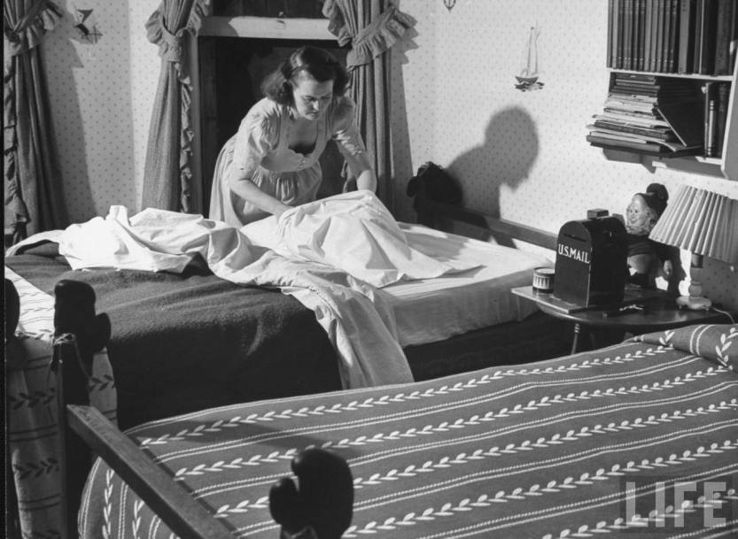 1940s housewife makes the beds